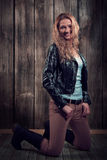 Beautiful fashion model with blond curly hair wearing black jacket, pants, and black tall boots in a pose on her knees Royalty Free Stock Image