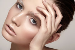 Beautiful fashion model face with winter make-up, snow eyebrows, shiny pure skin Royalty Free Stock Image