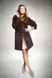 Beautiful fashion model in fur coat with cigarette Royalty Free Stock Images