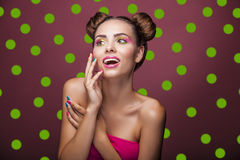 Beautiful fashion model girl with bright makeup and funny hair o. N a pink background in green peas, glamour, make-up, beauty Royalty Free Stock Image