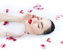 Beautiful fashion model girl taking milk bath, spa and skincare stock photo