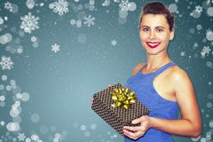 Beautiful fashion model girl with Xmas gift boxes against snowflakes on blue background. Young woman holding gifts on Christmas. Royalty Free Stock Photos
