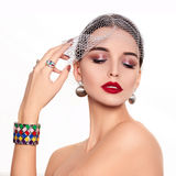 Beautiful and fashion model. On isolated white background. Beautiful young woman with stunning make-up and decorations in the form of rings and bracelets Stock Photography