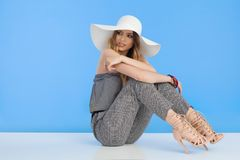 Beautiful Fashion Model In Jumpsuit And White Sun Hat Is Sitting And Looking Away Over Shoulder Stock Image