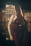 Beautiful fashion model poses with Louvre museum in background Royalty Free Stock Image
