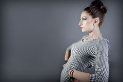 Beautiful fashion model posing. Young beautiful model posing with an elaborate makeup and  hair styling Stock Photography