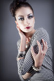 Beautiful fashion model posing. Young beautiful model posing with an elaborate makeup and hair styling royalty free stock photography