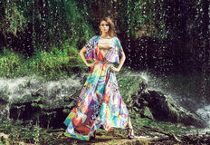 Beautiful fashion model posing in front of a waterfall Stock Image
