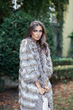 Beautiful fashion model posing in a fur coat outdoor Stock Photos