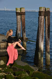 Beautiful fashion model posing at old ocean pier location Stock Photos