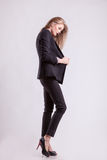 Beautiful fashion model posing in suit on grey background Royalty Free Stock Photos