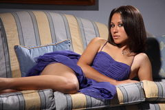Beautiful fashion model sexy pose lying on sofa Royalty Free Stock Photo
