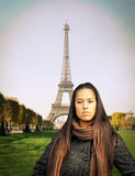 Beautiful fashion model standing against Eiffel tower Royalty Free Stock Image