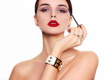 Beautiful and fashion model. A beautiful model on a white background mascara in hand Stock Image