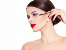 Beautiful and fashion model. A beautiful model on a white background mascara in hand Stock Images