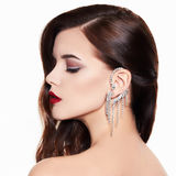 Beautiful and fashion model. Beautiful and model on a white background. Beautiful young woman with a stunning make-up and expensive earring in the ear Royalty Free Stock Photos