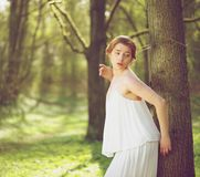 Beautiful fashion model in white dress standing outdoors royalty free stock photography