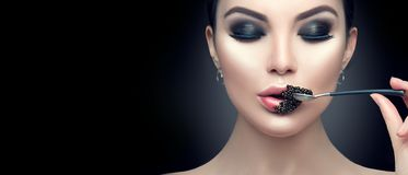 Beautiful fashion model woman eating black caviar. Beauty girl with caviar on her lips. Isolated on black background royalty free stock photos