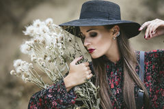 Beautiful fashion model woman with makeup and fancy dress outside on the background of sand royalty free stock photo