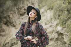Beautiful fashion model woman with makeup and fancy dress outside on the background of sand royalty free stock photography