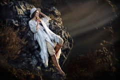 Beautiful fashion model woman posing in mountains at sunset royalty free stock photography