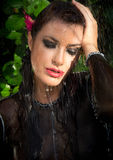 Beautiful Fashion Model Woman in Summer Rain. Gorgeous woman with downcast eyes wearing makeup and a trendy black outfit with her hand to her wet brunette hair Royalty Free Stock Image