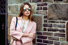 Beautiful fashion model woman wearing sunglasses and standing near brick wall.  Royalty Free Stock Image