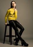 Beautiful fashion model with yellow jumper sitting Stock Image