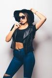Beautiful fashion mulatto girl wearing sunglasses and black hat. Over a white background Stock Photo