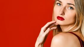 Fashion portrait of sexual blond woman with provocative glossy red lips over red background. stock photo