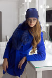 Beautiful fashion sexy elegant girl with long hair trendy blue cap on his head from evening sitting bright makeup and painting. Near the mirror Stock Images