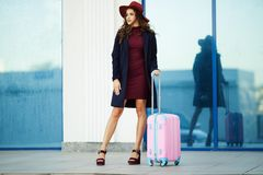 Beautiful happy girl is wearing fashion clothes and hat near airport with pink suitcase. Concept photo of people travel. Beautiful fashion tourist woman near Royalty Free Stock Photo