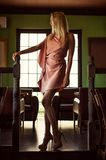 Beautiful fashion woman in pink dress. Beautiful fashion woman in asymmetrical gently pink dress in dark interior of cafe or restaurant stock photos