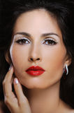 Beautiful fashion woman with bright makeup touches her perfect skin on face Royalty Free Stock Photo
