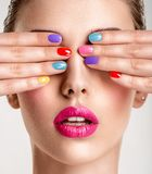 Beautiful fashion woman with a colored nails. Attractive white girl with multicolor manicure royalty free stock photo