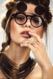 Beautiful fashion woman with creative make-up, hairstyle wearing glasses and jewelry. beauty face. Beautiful fashion woman with creative make-up and hairstyle royalty free stock image