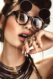 Beautiful fashion woman with creative make-up, hairstyle wearing glasses and jewelry. beauty face. stock photography