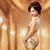 Beautiful fashion woman in gold dress, elegant lady in expensive Stock Images
