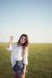 Beautiful and fashion woman on green field pointing with her hand Stock Photos