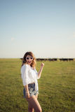 Beautiful and fashion woman on green field pointing with her hand Royalty Free Stock Images