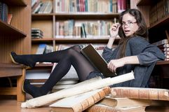 Beautiful and fashion woman in the library reading Royalty Free Stock Image