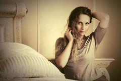 Beautiful fashion woman with long curly hairs in a bedroom Stock Photos