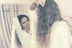 Beautiful fashion woman with long curly hairs looking in the mirror royalty free stock images