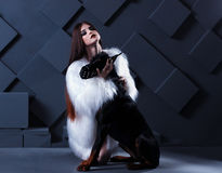 Beautiful fashion woman with long hair sitting with black doberman dog Royalty Free Stock Photo