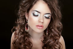 Beautiful fashion woman with makeup, long wavy hair and earrings Royalty Free Stock Photos