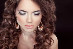 Beautiful fashion woman with makeup, long wavy hair and luxury e Stock Image