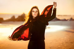 Beautiful fashion woman posing on the ocean beach wearing autumn clothes at sunset time Royalty Free Stock Photography