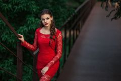 Beautiful fashion woman posing in red dress with creative hairstyle. Trendy urban portrait on green background stock images