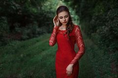 Beautiful fashion woman posing in red dress with creative hairstyle. Trendy urban portrait on green background stock photos