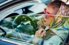 Beautiful fashion woman with red lips and sunglasses in the car. royalty free stock photo
